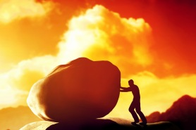 Man pushing a giant, heavy stone, rock over the mountain.